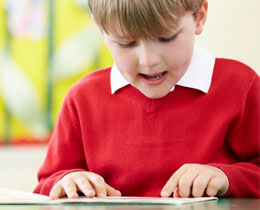 boy reading red jumper